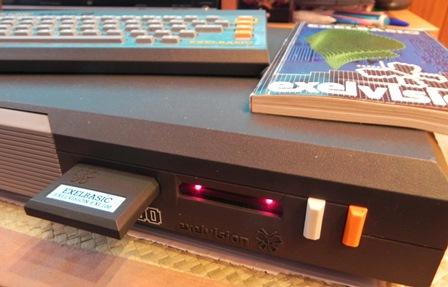 Détail de la face avant de l'EXL 100 : le lecteur de cartouche, le récepteur infrarouge, les boutons reset et marche/arrêt